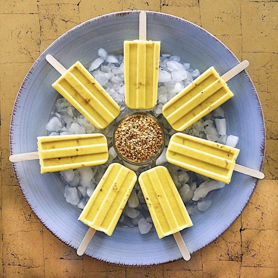 Dairy-free golden milk popsicles rest on a bed of ice on a blue plate in a circle, with a glass bowl of bee pollen in the center.