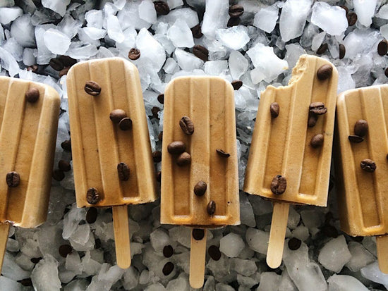Vegan and dairy-free cold brew tahini popsicles lie on a bed of ice with coffee beans sprinkled on top.