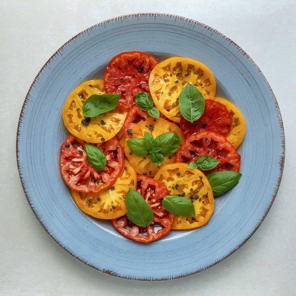 Sliced red and yellow farm fresh tomatoes on a blue plate, garnished with sea salt, pepper, and basil leaves.