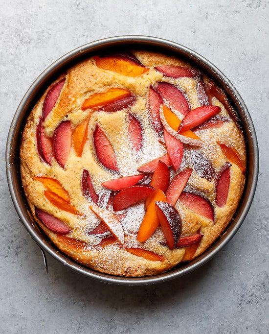 Aerial shot of a plum and apricot cake in a baking pan sprinted with icing sugar.