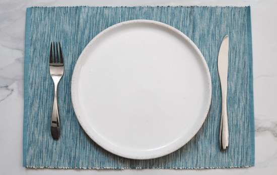 An empty white plate on a blue placemat next to a silver fork on a knife, all on a white marble countertop.