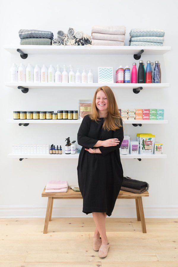 A middle aged woman with red hair stands grinning in a store, standing in front of white shelves filled with natural beauty and wellness products.