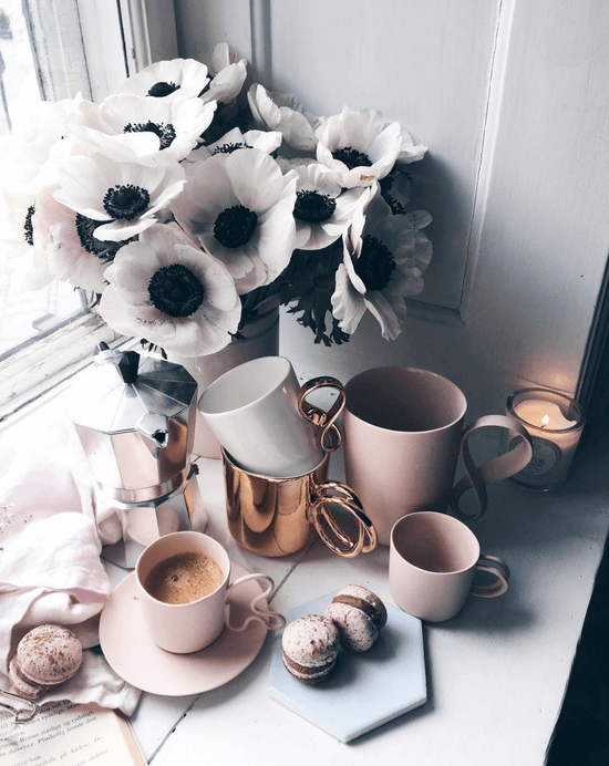 Pink coffee cups on pink saucers sit on a windowsill surrounded by vanilla macarons and next to a vase full of big white flowers.