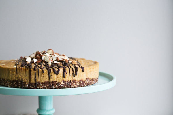raw almond cake on a mint green cake stand, drizzled with chocoalte