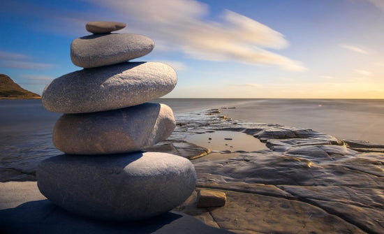A rock cairn on a rocky shoreline in front of the glossy ocean at sunrise.