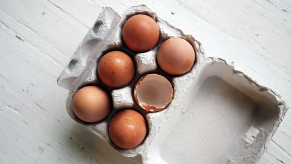 Aerial view of a half dozen brown eggs in a cardboard carton with one egg cracked open and empty.