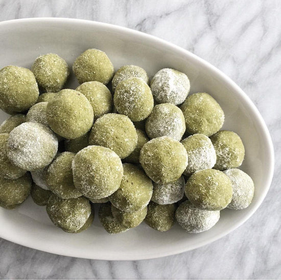 stack of coconut dusted matcha balls on marble counter