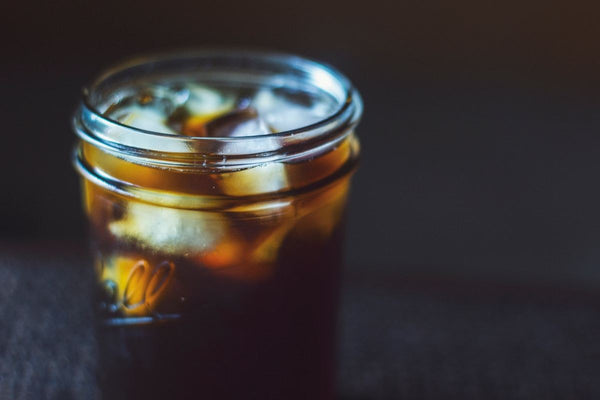 dark image of cold brew in mason jar with ice