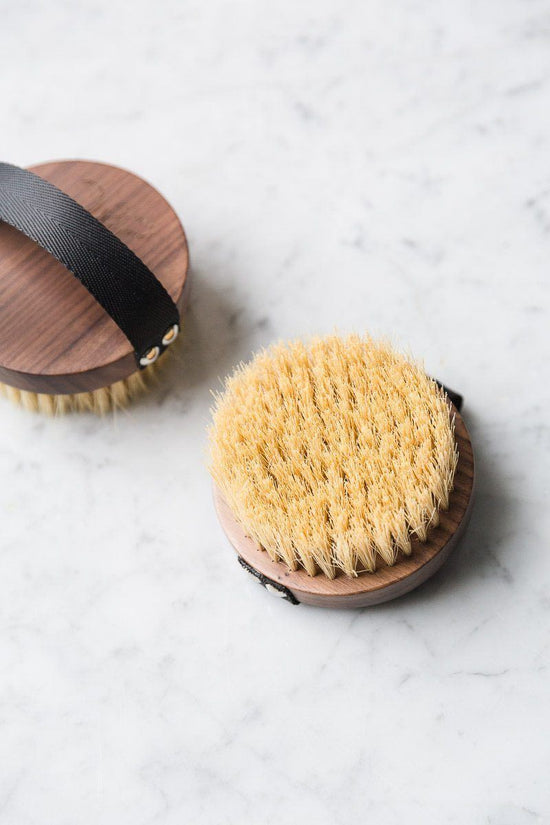 Two vegan dry skin brushes lie against a white marble background.