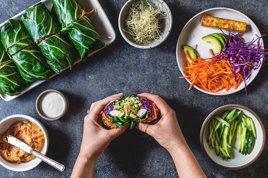 extra large lettuce wraps being held by hands with ingredients in bowls shredded carrot sprouts