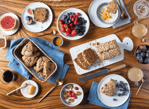 Aerial view of a breakfast spread on a wooden table, including gluten-free and refined sugar-free scones, loaf, berries, honeycomb, grapefruit halves, figs, and coffee.