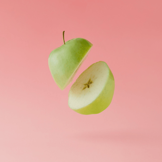A Granny Smith apple sliced in half floats in front of a bright pink background.