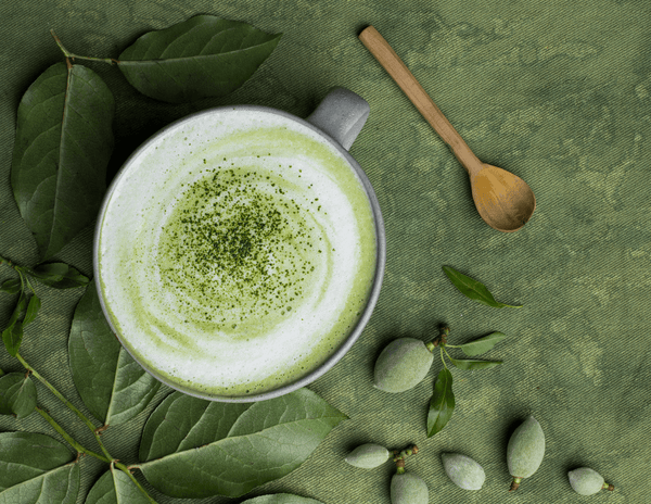 A frothy green matcha latte in a mug with sprinkled matcha on top, on a green backdrop next to green leaves and a wooden spoon.