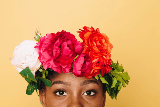 The upper half of a woman's face comes into shot wearing a crown of brightly colored flowers against a yellow background.