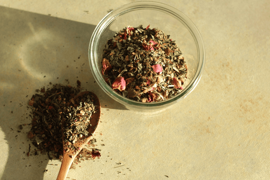 A glass jar and wooden spoon of an herbal infusion with holy basil, Moringa, lavender, dried rose petals, and licorice root.