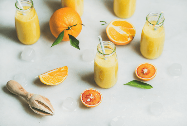 Small glass jugs of freshly squeeze orange juice with paper straws, surrounded by orange slices, orange leaves, and a lemon press.