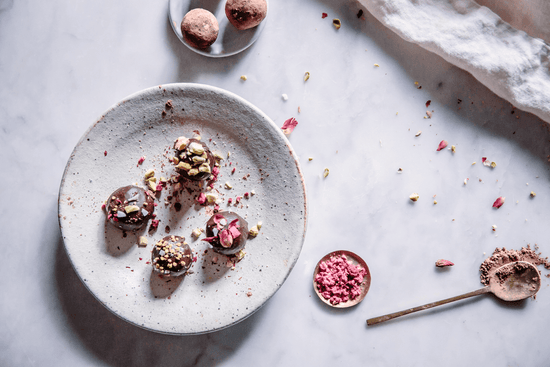 Adaptogenic energy bliss bites topped coated with chocolate and topped with chopped pistachios, dried rose petals, and bee pollen sit on a white ceramic plate.