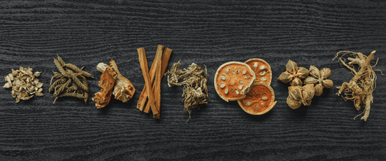 Dried herbs and spices in a line against a dark background.