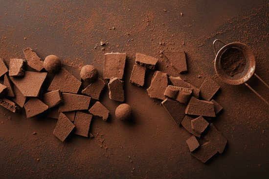 Aerial view of broken chocolate bars and chocolate truffles scattered across a dark backdrop, covered in raw cacao powder, next to a sieve full of raw cacao powder.