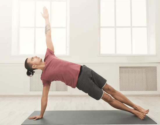 A fit young man on a yoga mat does a side plank in a brightly lit and white yoga studio.