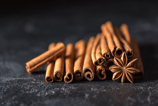 A stack of warm brown cinnamon sticks against a black backdrop with a dried star anise pod.