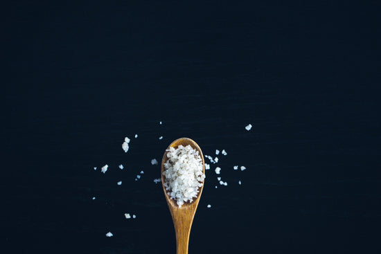 A wood spoon of crisp white sea salt on a dark blue background with sprinkles of salt.