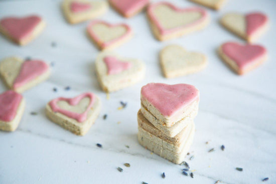lavender lemon shortbread cut into heart shapes with lavender petals in foreground