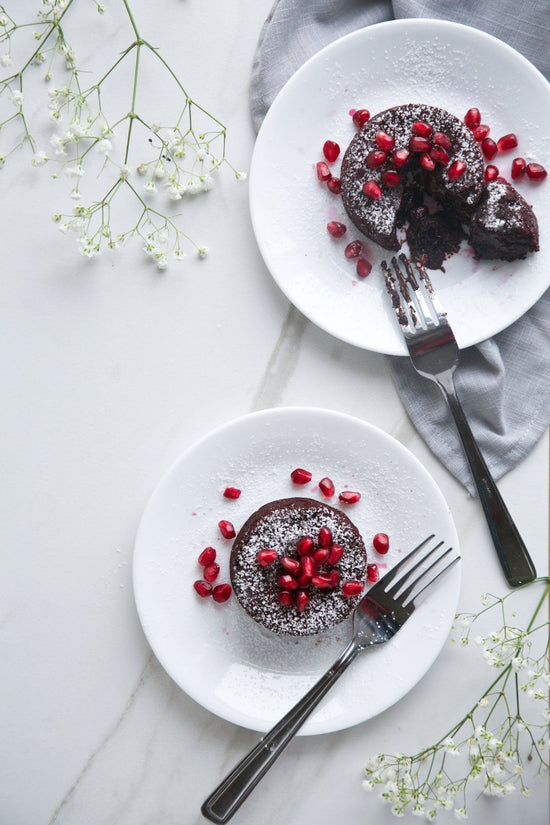 two plated red velvet chocolate lava cakes garnished with pomegranate