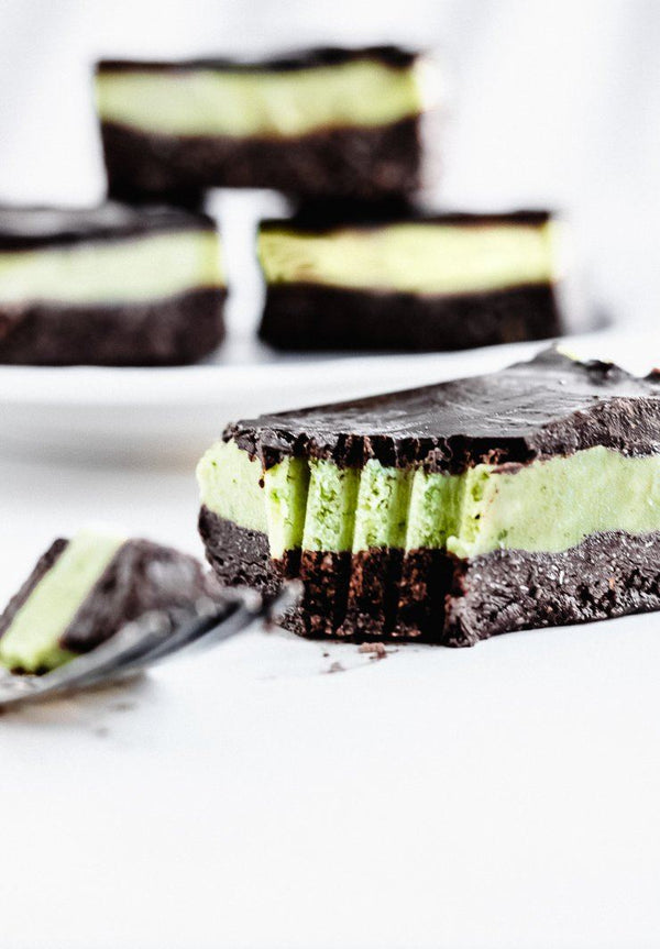 close up on mint chocolate avocado bar with fork scratches in it and three more bars in the background
