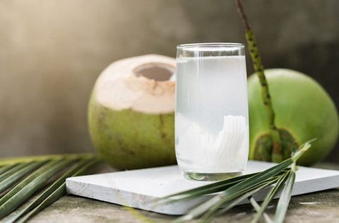 coconut water in glass on marble counter with coconuts in back