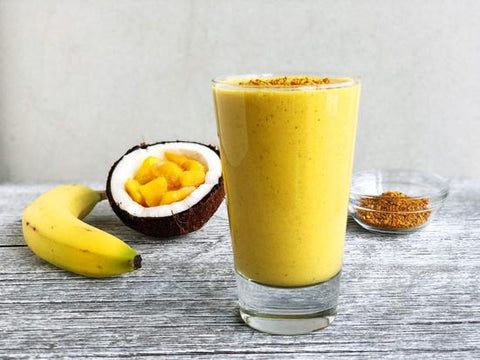 a tropical turmeric smoothie topped with bee pollen in front of a banana, a halved coconut filled with mango and a glass of bee pollen
