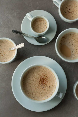 ceramic bowls and mugs of frothy cardamom spiced dandelion root latte