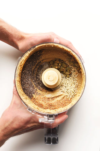 two male hands holding a kitchen mixer filled with sunflower seed butter