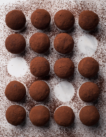 aerial view of vegan chocolate truffles with raw cacao sprinkled around