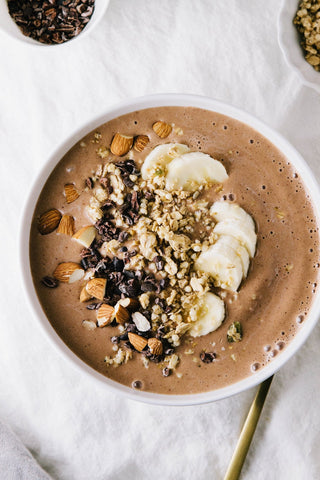 a chocolate smoothie bowl topped with chopped nuts cacao nibs and bananas