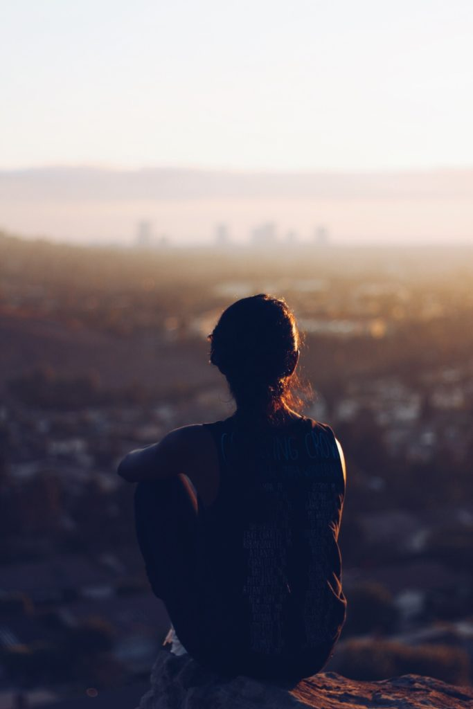 The silhouette of a young girl sitting on the edge of a cliff looking over the hazy skyline of Los Angeles.
