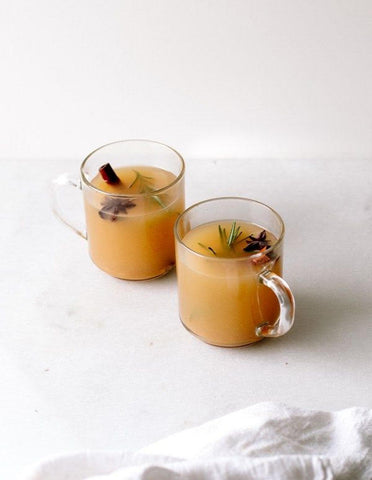 two glass mugs of apple cider with cinnamon sticks and cloves