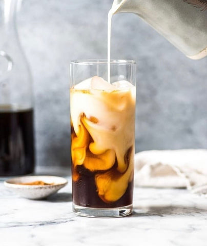 milk poured into tall glass of cold coffee with ice on a table with a jug in the background