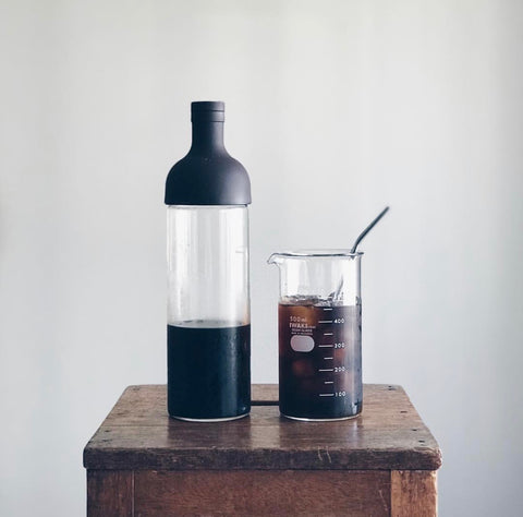 cold brew coffee in scientific beaker on wooden stool