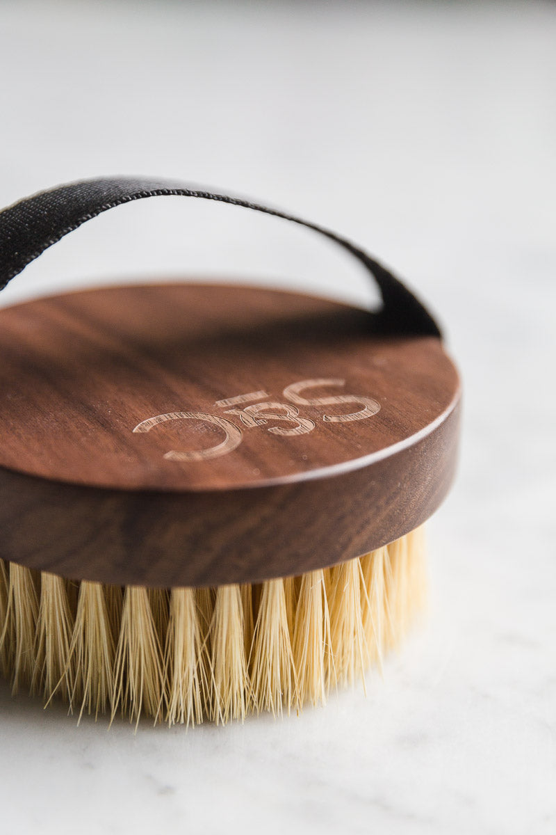 Close-up shot of a wooden vegan dry skin brush with a black handle on a white marble background.