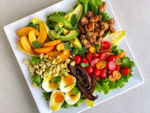 square plate with cut up vegetables avocado eggs peppers nuts