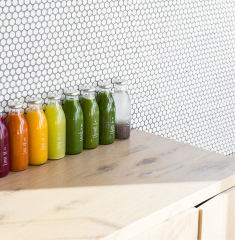 greenhouse juice in glass bottles lined up on a wooden counter in front of a tiled wall