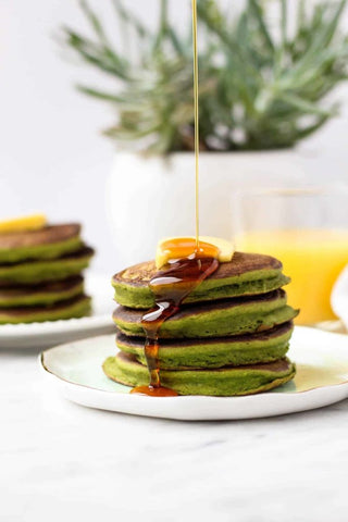 stack of green pancakes with syrup poured from height
