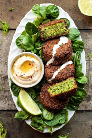 green falafals plated on lettuce leaves halved served with tahini