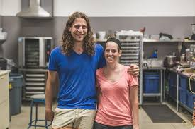 a young man and young woman stand together and smile in an industrial kitchen