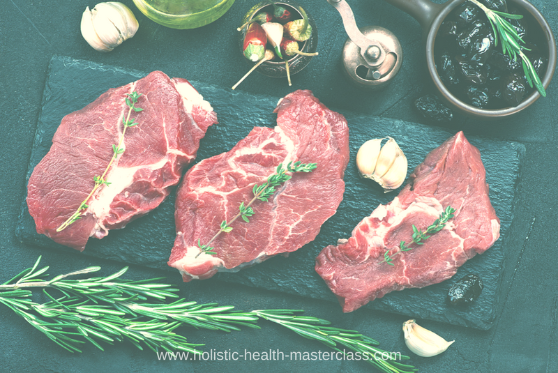 Three raw steak cuts rest on a stone slab surrounded by fresh rosemary, garlic, black olives, and fresh chili peppers.
