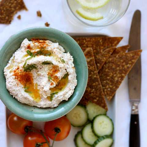 nut pulp hummus in a blue dish garnished with vegetables surrounded by crackers cucumbers and tomatoes