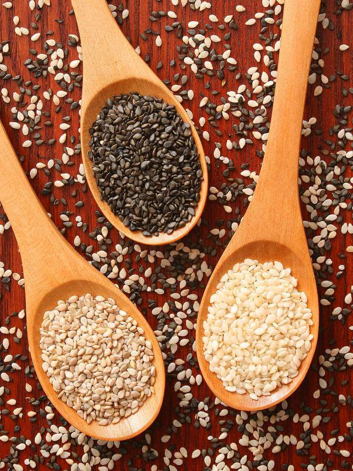 Three wooden spoons filled with black and white sesame seeds lie on a red wooden backdrop surrounded by sprinkled sesame seeds.