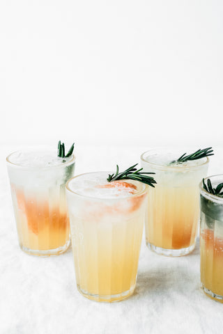 four glasses filled with rosemary honey grapefruit spritzer garnished with rosemary