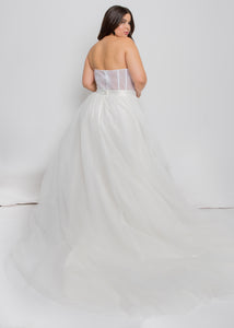 Gorgeous bridal gowns for all body shapes: plus size, curvy, or petite brides. Try on our wedding dresses at home. Size 0-30. Comfortable. Convenient. Fun. Lace or satin. Mermaid or A-line. The tulle corset top lends an edge to the more classic and enchanting tulle skirt. Ivory corset detailing over a nude lining offers some color contrast and an undeniable cool look. Tulle A-Line skirt that offers a soft volume for increased interest and romance as you glide through your wedding.